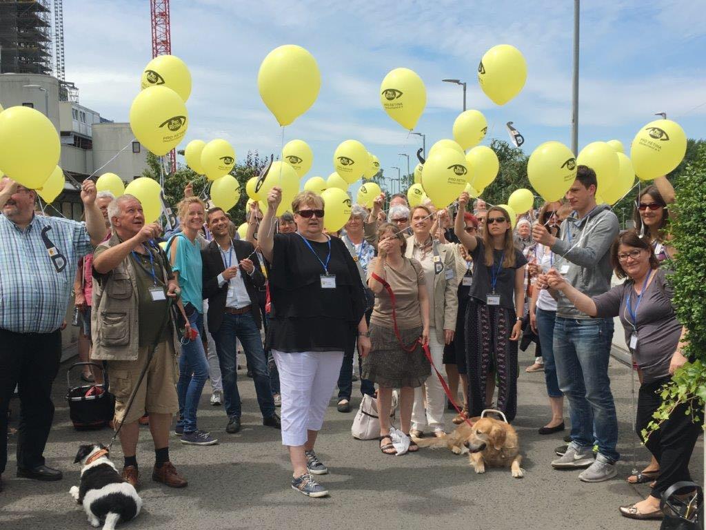 Auf dem Bild sind Menschen im freien von der Pro Retina e. V. mit Luftballons abgebildet, einige davon mit Blindenführhund.