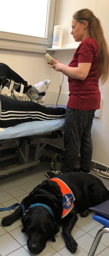Heike Ferber liegt auf einer Behandlungsbank. Am Boden liegt ihr schwarzer Blindenführhund mit ihrer Kenndecke sowie die Physiotherapeutin, die eine Fernbedienung zur Einstellung der Behandlungsbank in Händen hält.